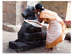 Whispering into the ear of the Nandi. Perhaps to take a message to Shiva!